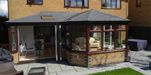 Rosewood conservatory frames with Guardian Grey slate on conservatory roof